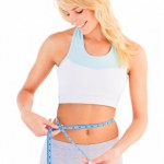 Young blond girl measuring her waist over white background